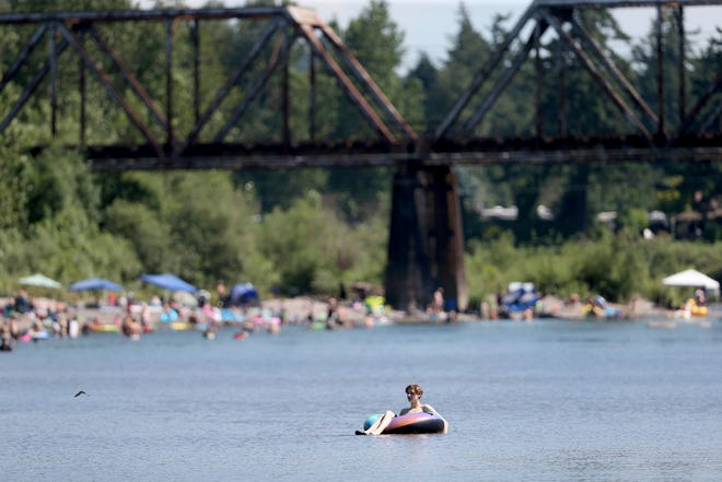 People gather at the Sandy River Delta near Troutdale to cool off during the start of what should be a record-setting heat wave on June 25. The Pacific Northwest sweltered Friday as a historic heat wave hit Washington and Oregon, with temperatures in many areas expected to top out 25 to 30 degrees above normal in the coming days.