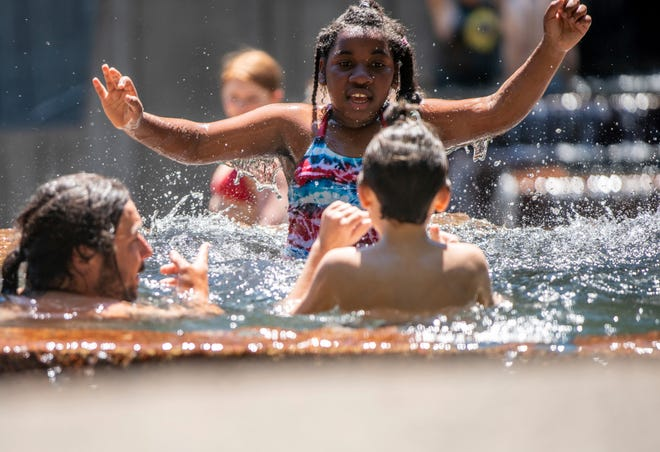 As the city temperature surpasses 110 degrees, people cool off at Keller Fountain Park on June 27 in Portland, Oregon.