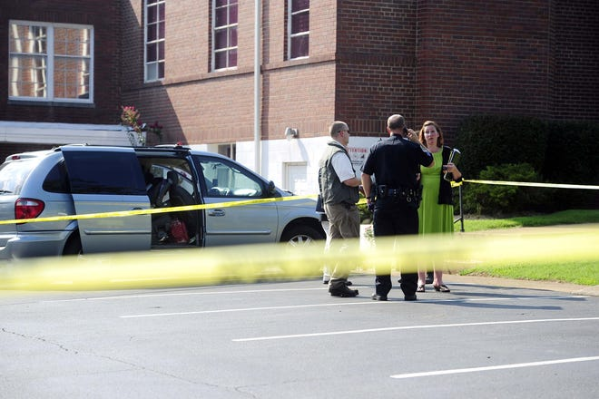 Investigators survey the scene in Donelson, Tennessee, where a 5-month-old boy was found dead after being left inside an overheated minivan by his mother on Tuesday, Aug. 7, 2012.