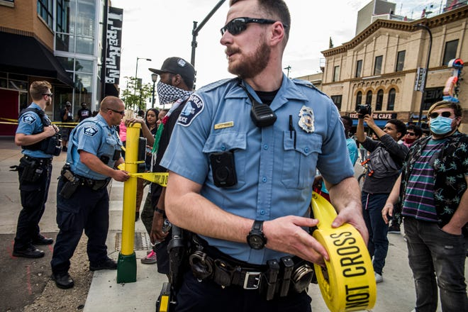 Police investigate a shooting as protesters gather on Thursday, June 3, 2021 in Minneapolis. Crowds vandalized buildings and stole from businesses in Minneapolis' Uptown neighborhood after officials said a man was fatally shot by authorities.