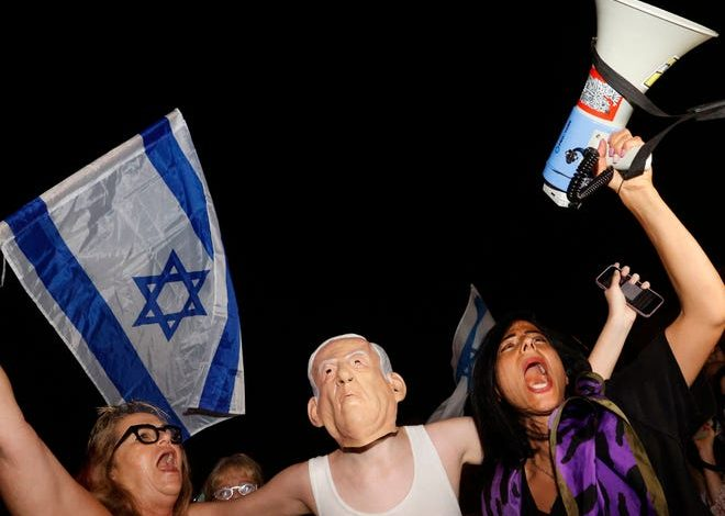 """An Israeli protester wears a mask of Prime Minister Benjamin Netanyahu and a T-shirt with a slogan reading in Hebrew: """"the ceremony is over"""" during a demonstration in support of the opposition for the formation of a government, on May 31, 2021 in Tel Aviv."""