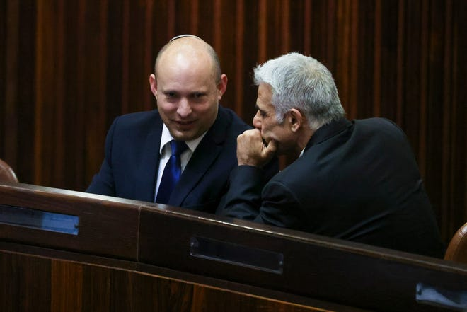 Yamina party leader Naftali Bennett, left, smiles as he speaks to Yesh Atid party leader Yair Lapid during a special session of the Knesset, whereby Israeli lawmakers elect a new president, at the plenum in the Knesset, Israel's parliament, in Jerusalem on Wednesday, June 2, 2021.
