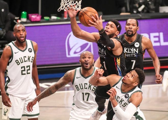The Brooklyn Nets' Bruce Brown jumps over the Milwaukee Bucks' P.J. Tucker and Giannis Antetokounmpo to grab a rebound.