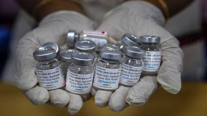 A health worker displays vials of COVID-19 vaccines in