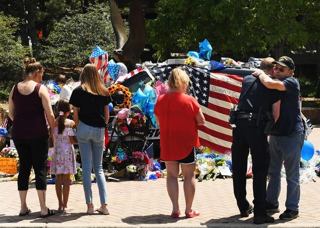 Pat Nevin, right, who said two of his three children work in law enforcement, hugs Arvada Police Officer Shaun Granmoe outside a memorial for Arvada Police Officer Gordon Beesley on June 22, 2021 in Arvada, Colo.