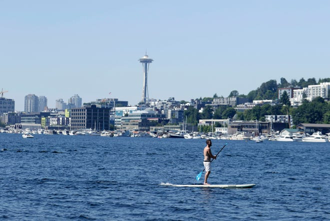 A person rides on a paddle board on Lake Union during a heat wave hitting the Pacific Northwest, Sunday, June 27, 2021, in Seattle. Yesterday set a record high for the day with more record highs expected today and Monday. (AP Photo/John Froschauer)