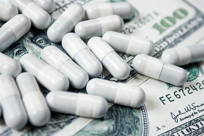 Prescription capsules laid atop a messy pile of one hundred dollar bills.
