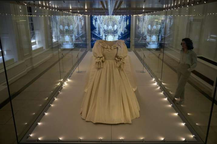 India Tv - A staff member poses for photographers next to the wedding dress of Britain's Princess Diana during a media preview for the