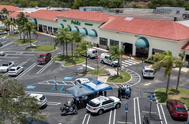 Police gather at the Publix shopping center where police say 3 people were shot and killed inside the store in Royal Palm Beach, Florida on June 10, 2021.