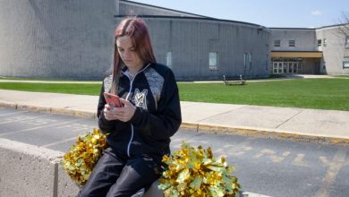 Brandi Levy wears her former cheerleading outfit as she looks at her mobile phone while sitting outside Mahanoy Area High School in Mahanoy City, Pa., on April 4, 2021. Photo provided by the American Civil Liberties Union.