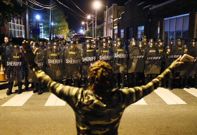 A protester stands with her arms raised as law enforcement officials in riot gear force people off a street as they protest the killing of Andrew Brown Jr. on April 28, 2021 in Elizabeth City, North Carolina.