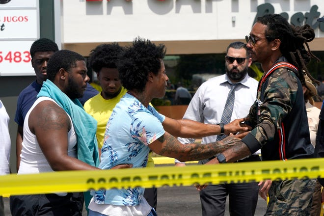 Clayton Dillard, center, is restrained by friends at the scene of a shooting outside a banquet hall in Miami, seeking information about a family member, Sunday, May 30, 2021.