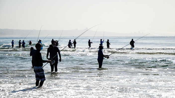 Fisherman with rods standing in the sea off Durban, South Africa - Saturday 26 June 2021