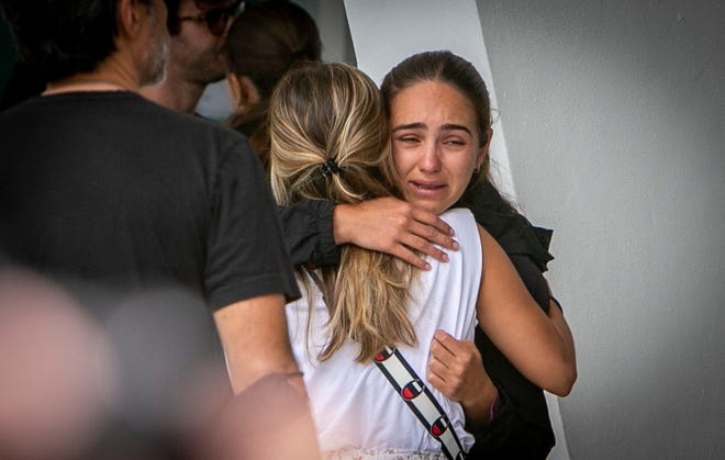 Two women comfort each other at the Surfside community center where friends and family of those missing following the collapse of a residential building wait for new developments in the search for their loved ones, Friday, June 25, 2021, in Surfside, Fla.