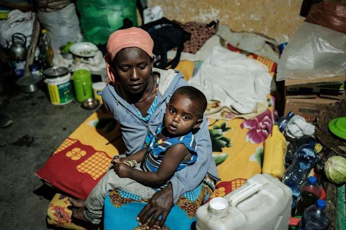 A mother, who fled the violence in Ethiopia's Tigray region, holds her child in a classroom.