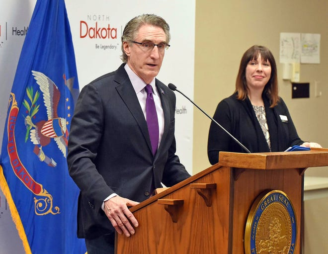 Molly Howell, immunization program manager for the North Dakota Department of Health, listens as Gov. Doug Burgum talks about the COVID-19 pandemic during a press conference on March 20, 2020, in Bismarck, N.D.