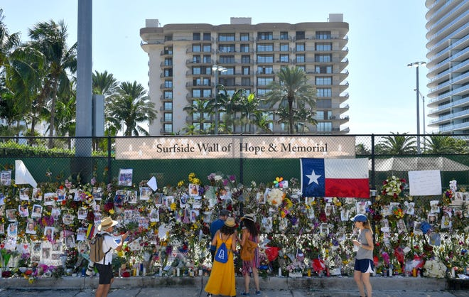 The Champlain Towers South condominium is visible behind the memorial wall for people missing in the collapse of the building in Surfside Florida.