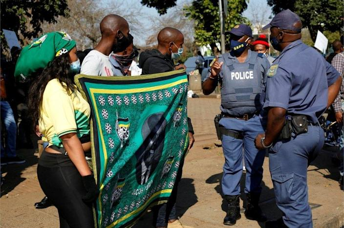 Police move flag-wielding supporters of former South African president Jacob Zuma who were protesting in front of the High Court in Pietermaritzburg, South Africa, on 6 July, 2021