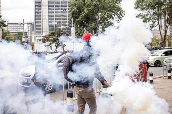 A man holds a tear gas canister thrown by Kenyan police officers during a protest against police brutality and harassment, especially against the poor, in Nairobi on July 7, 2021.
