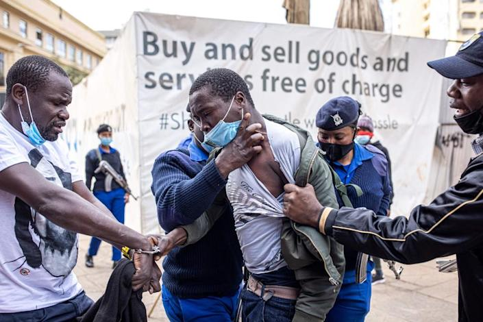Kenyan police officers arrest protesters during a march