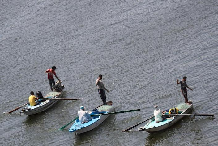 Men fish from boats on the River Nile in Cairo, Egypt