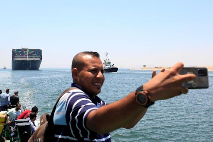 """A man takes a selfie as Ever Given, one of the world""""s largest container ships, sets sail to leave at the Suez Canal after the canal authority reached a settlement with the vessel""""s owner and insurers, in Ismailia"""