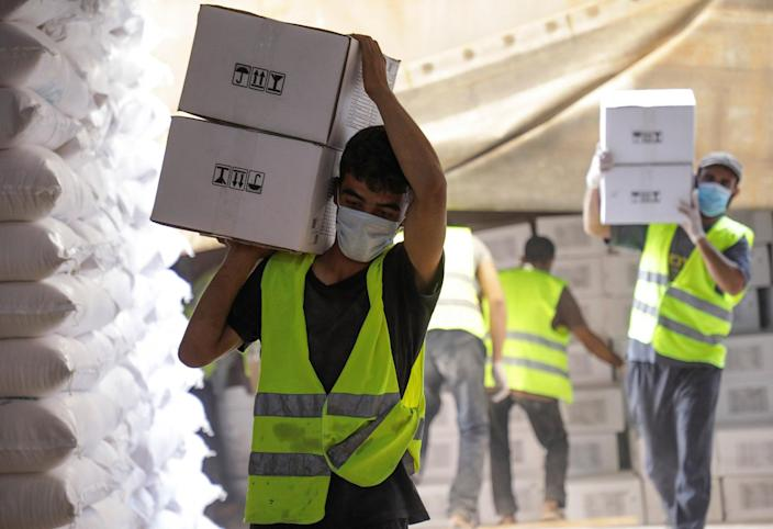 Image: Workers carry boxes of humanitarian aid near Bab al-Hawa crossing at the Syrian-Turkish border. (Mahmoud Hassano / Reuters)