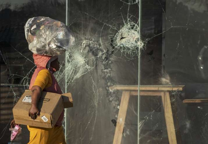 India Tv - A woman carrying groceries on her head, walks past a damaged KFC fast food restaurant at Naledi shopping complex in Vosloorus, east of Johannesburg, South Africa.