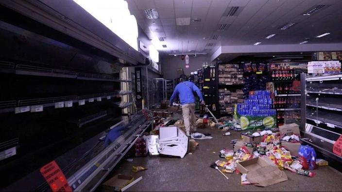 A self-armed local looks for looters inside a supermarket following protests that have widened into looting, in Durban, South Africa July 13, 2021, in this screen grab taken from a video