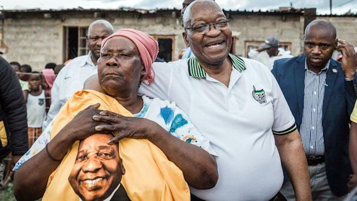 Former South African President and former president of the ruling party African National Congress (ANC) Jacob Zuma (2ndR) is held tightly by ANC supporter Maria Mandweni during a door to door campaign visit in Shakaskraal township, on April 16, 2019