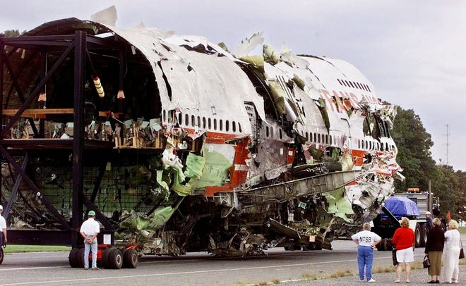 Luz Palaez, far right, who lost her daughter on TWA flight 800, Joan Holst, second from right, who lost her son, Marge Gross, second from left, who lost her brother and Betty Scott, a member of the National Transportation Safety Board, look on as the reconstruction of Flight 800 is moved to a smaller hanger in Calverton, New York, Tuesday, Sept., 14, 1999.