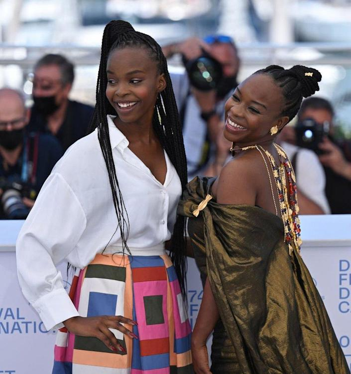 Two women smile and pose on the red carpet.
