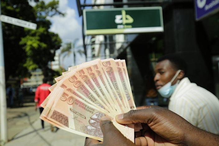 A man holds a fan of the new Zimbabwe 50 dollar note in Harare.