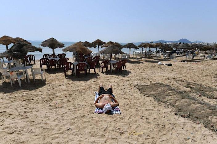 A man lies on a nearly deserted beach in Tunis.