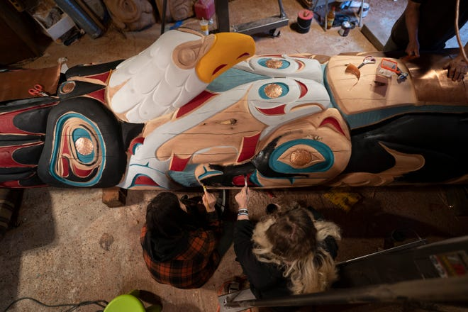 Two Lummi nation House of Tears Carvers artisans work on the 25-foot totem pole that is journeying across the U.S. with Native American activists to highlight the need to protect sacred lands.