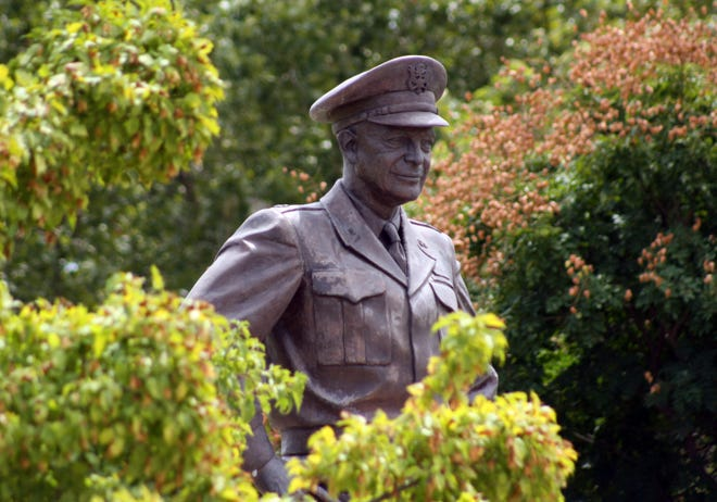 A bronze statue of Gen. Dwight D. Eisenhower stands over the grounds of the library, museum and boyhood home of the 34th president in Abilene, Kan. The federal government will shut down the library and museum Monday as the delta variant fuels a growing number of new COVID-19 cases in Kansas.