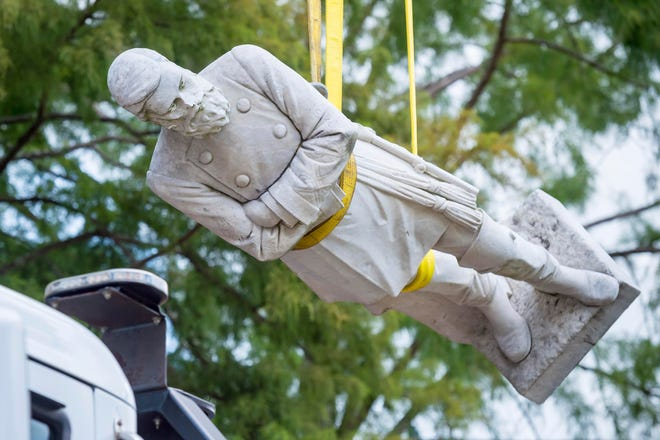 The statue of Confederate Gen. Alfred Mouton is removed from the front of city hall in Lafayette, La., where it had stood for 99 years.