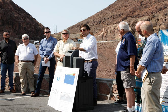 Kyle Roerink of Great Basin Water Network, center, speaks during a news conference at the Hoover Dam in the Arizona side to share demands for managing the shrinking Colorado River.