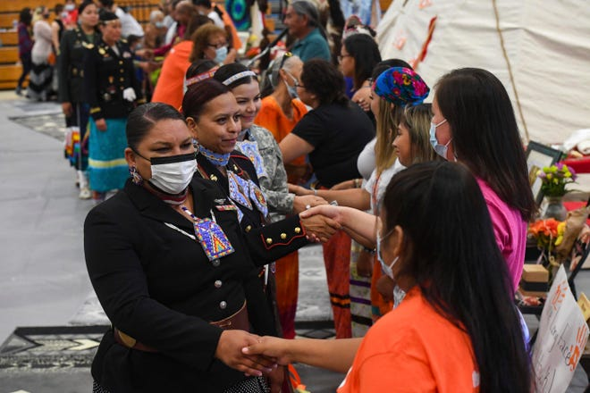 The Rosebud Sioux tribal color guard shakes hands with members of the youth council that started the mission to bring the remains of nine children home from Pennsylvania at the Sinte Gleska University Student Multicultural Center in Rosebud, S.D.