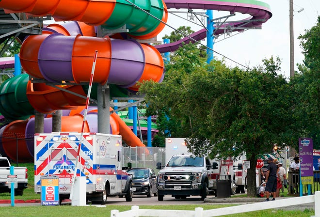 Emergency personnel vehicles are parked near the scene where people were being treated after a chemical leak at Six Flags Hurricane Harbor Splashtown in Spring, Texas.