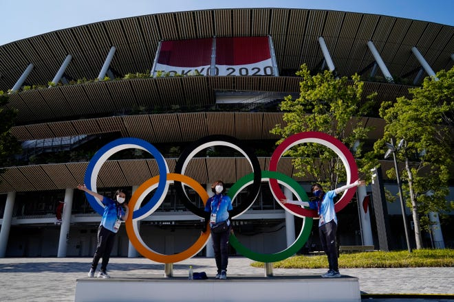 Volunteers pose with the Olympic rings during the opening ceremony for the Tokyo 2020 Olympic Summer Games at Olympic Stadium.