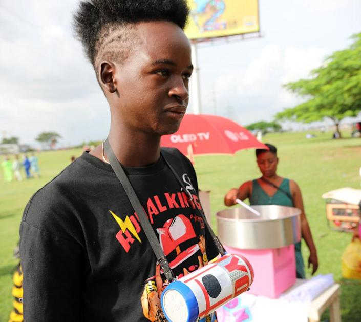 A Fulani boy with a punk hairdo and radio across his chest