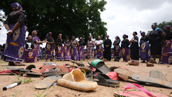 Parents of kidnapped students from Bethel Baptist High School, in Nigeria's Kaduna state, stand by shoes left behind after the attack - July 2021