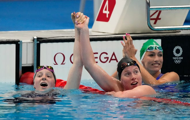 Lydia Jacoby (USA), Tatjana Schoenmaker (South Africa) and Lilly King (USA) react after finishing first, second and third in the women's 100-meter breaststroke.