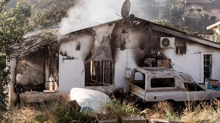 A picture taken on July 16, 2021 shows a house destroyed after angry mobs set fire to homes in Duffs Road near Phoenix