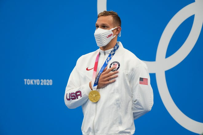 Caeleb Dressel listens to the national anthem at the medals ceremony after winning gold in the men's 100-meter butterfly.