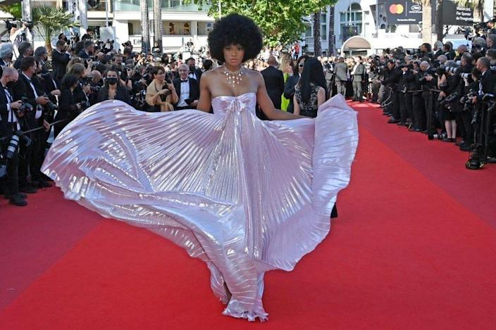 A woman poses in an iridescent dress on the red carpet.