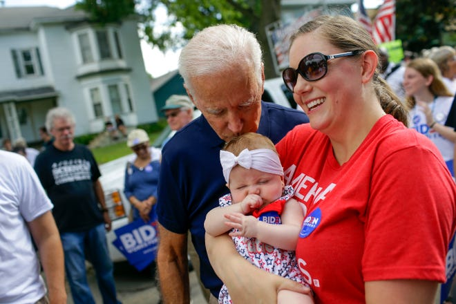 Democratic presidential candidate Joe Biden kisses Ashley Blasberg on her head as her mother Erin Blasberg looks on during the Fourth of July parade on July 4, 2019 in Independence, Iowa.