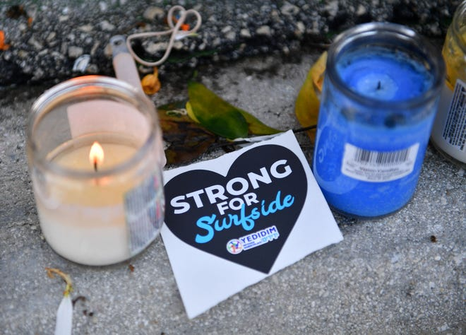 Surfside Strong stickers and candle are among the items left at the Surfside memorial wall on July 4, 2021. Recovery efforts at the Champlain Towers South condominium in Surfside, Fla. were suspended while crews begin preparing the remaining structure for demolition.