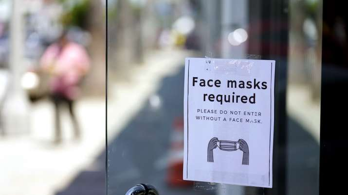 A sign advises shoppers to wear masks outside of a store,